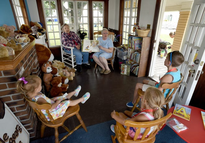 Margo Zieske (right) along with Judy Treadwill read a story about the Little Brown Bear to the Witbeck children; Charlotte, 3, Ellliott, 6, and Gabriel, 8, inside the Little Brown Bear House at the Monroe County Fair Tuesday.
