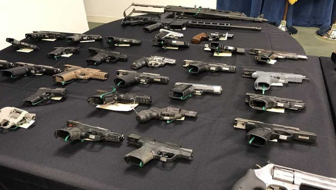 U.S. law enforcement authorities display guns taken off the streets of Lawrence in 2019. Eighteen of the 32 people arrested were members or associates of the Trinitarios street gang in Lawrence, according to investigators. (WCVB)