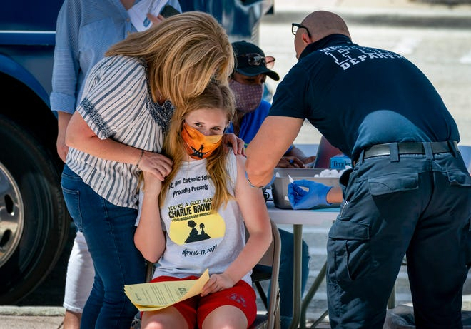 Jennifer Loyless, holds her daughter, Avery, 12, as she prepares to receive a COVID-19 vaccine at a mobile site at a Health Care District of Palm Beach County bus in West Palm Beach, Florida on May 14, 2021. GREG LOVETT/PALM BEACH POST