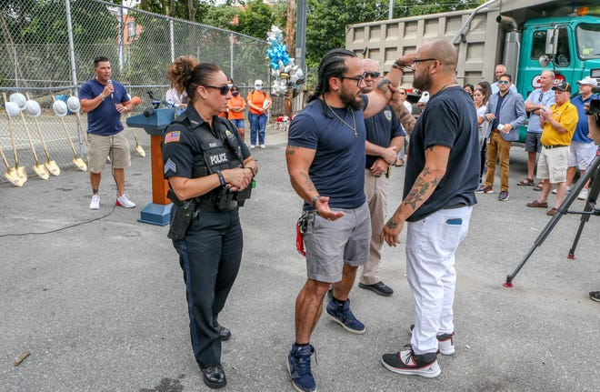 Community activist James Fernandez, right, rejects state Sen. Jonathon Acosta's reaching out to him during a disagreement Tuesday at the Central Falls groundbreaking for two tennis courts. Fernandez was opposed to displacing the Leo Labossiere basketball court for the project.
