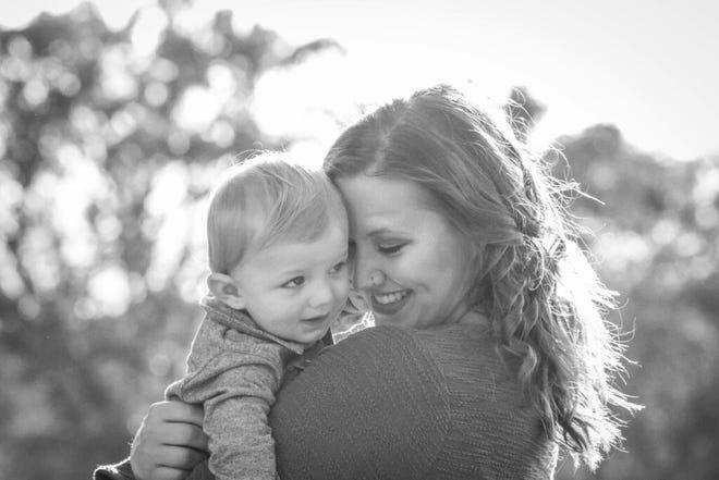 Webster Groves High School teacher Jaime Schwartz Adamski holds her son Arlo. Photo by Heather Koelling
