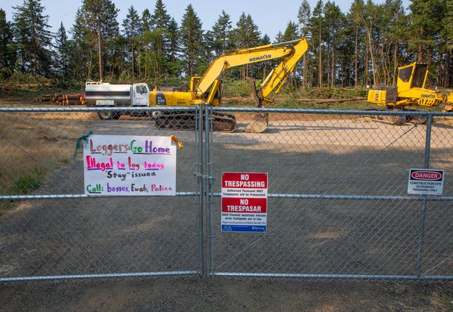 A protest sign hangs on a fence surrounding a Eugene Water & Electric Board property in south Eugene after a Land Use Board of Appeals order blocked logging on the site.