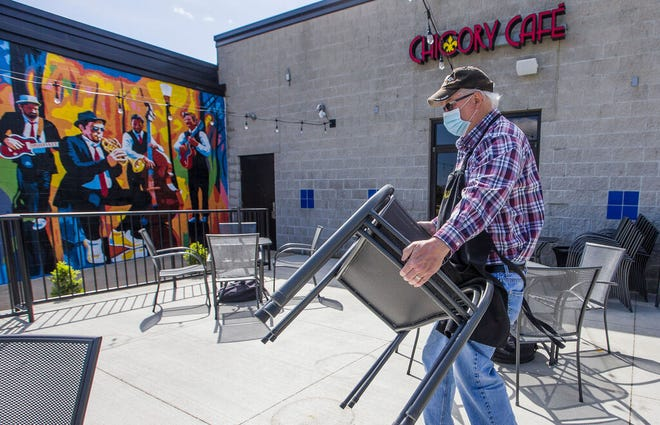 Phil Schreiber works to set up the outdoor dining area to comply with state mandated social distancing orders at Chicory Cafe's Mishawaka location in May 2020.