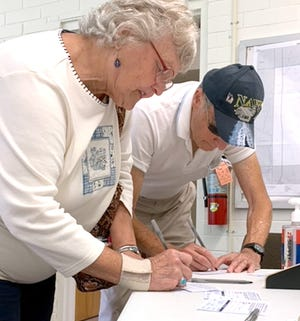 Pat and Fred Musser sign in to vote Tuesday at Park Township Hall.