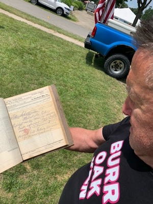 Ken Krayer shows a log documenting railroad loads at the former Sheffield Manufacturing building in Burr Oak. Krayer purchased the building earlier this summer and is in the process of renovating it.