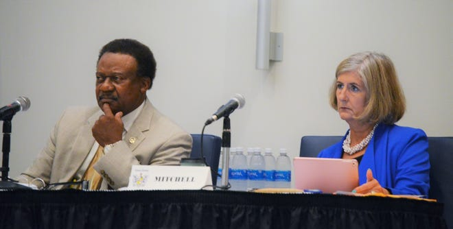 Theron McCabe and E.T. Mitchell of the Craven County Board of Commissioners listen as members of the public speak on the board's resolution opposing the teaching of critical race theory.