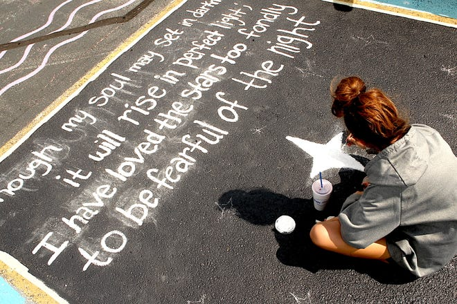 Italy Lewis paints her parking spot at the Bedford North Lawrence parking lot Monday afternoon. The quote is from poet Sarah Williams. Students in North Lawrence Community Schools and Mitchell Community Schools go back to school Wednesday.