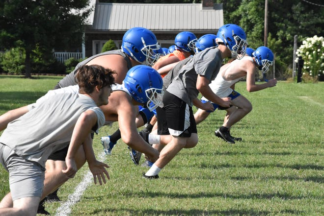 Mitchell's linemen take off from the goal line during conditioning at the end of their first official practice of the season.