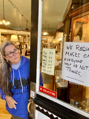 Marshall business owner Cindy Heath examines the new sign on her door asking customers to mask up before entering Just-Bead-It on Aug. 3 2021.