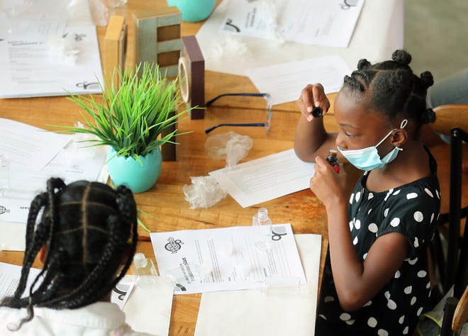 Adaiah Stevens, 7, smells essential oils as she decides which one to add to her shampoo and body wash during the Love Me For Me Young Mind Big Business program at the Marvin Williams Center in Bremerton on Monday.