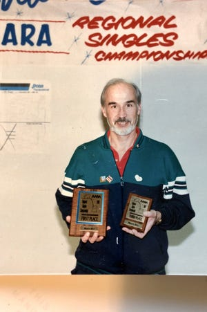 Charlie Hamon holds trophies from a regional racquetball tournament. The longtime Bremerton doctor, now 84, became one of the top racquetball players in the masters age group.