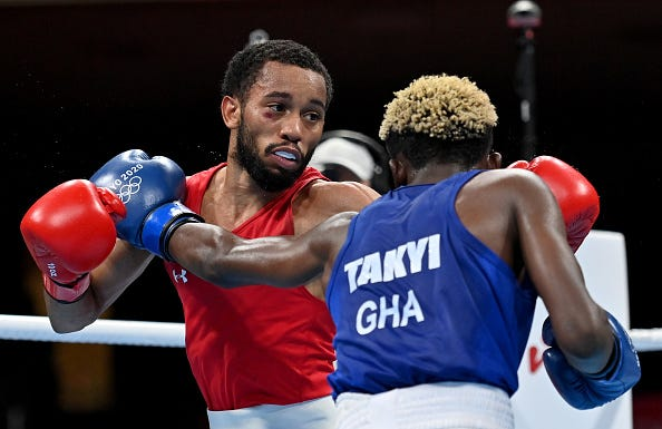 Duke Ragan (red) of Team the United States exchanges punches with Samuel Takyi of Team Ghana during the Men's Feather (52-57kg) semi final on day eleven of the Tokyo 2020 Olympic Games at Kokugikan Arena on August 03, 2021 in Tokyo, Japan.