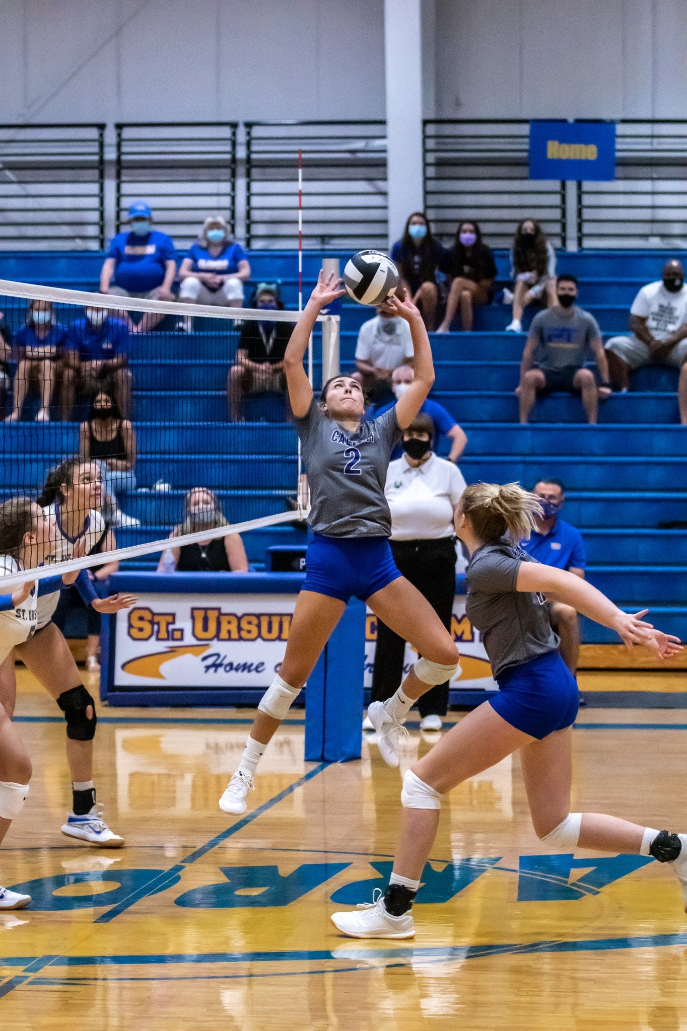 Emma White of Calvert sets up her teammate for a kill in a match with St. Ursula.