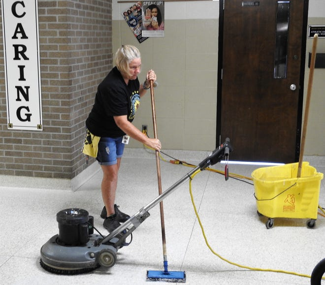 Dottie Dorsey mops floors to prepare for polishing at River View High School. Extensive cleaning is being done this summer to prepare for the return of students for for the 2021 to 2022 school year.