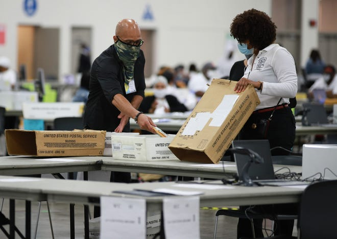 Election day poll workers count absentee ballots at the central counting board at the TCF Center in Detroit on August 3, 2021.