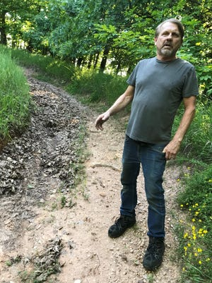 Joe Yunk of Kewaunee, standing on a eroded trail at  Riverview ATV Park, says Kewaunee County should do more to prevent erosion at the park, although county officials say they've been working on the issue.