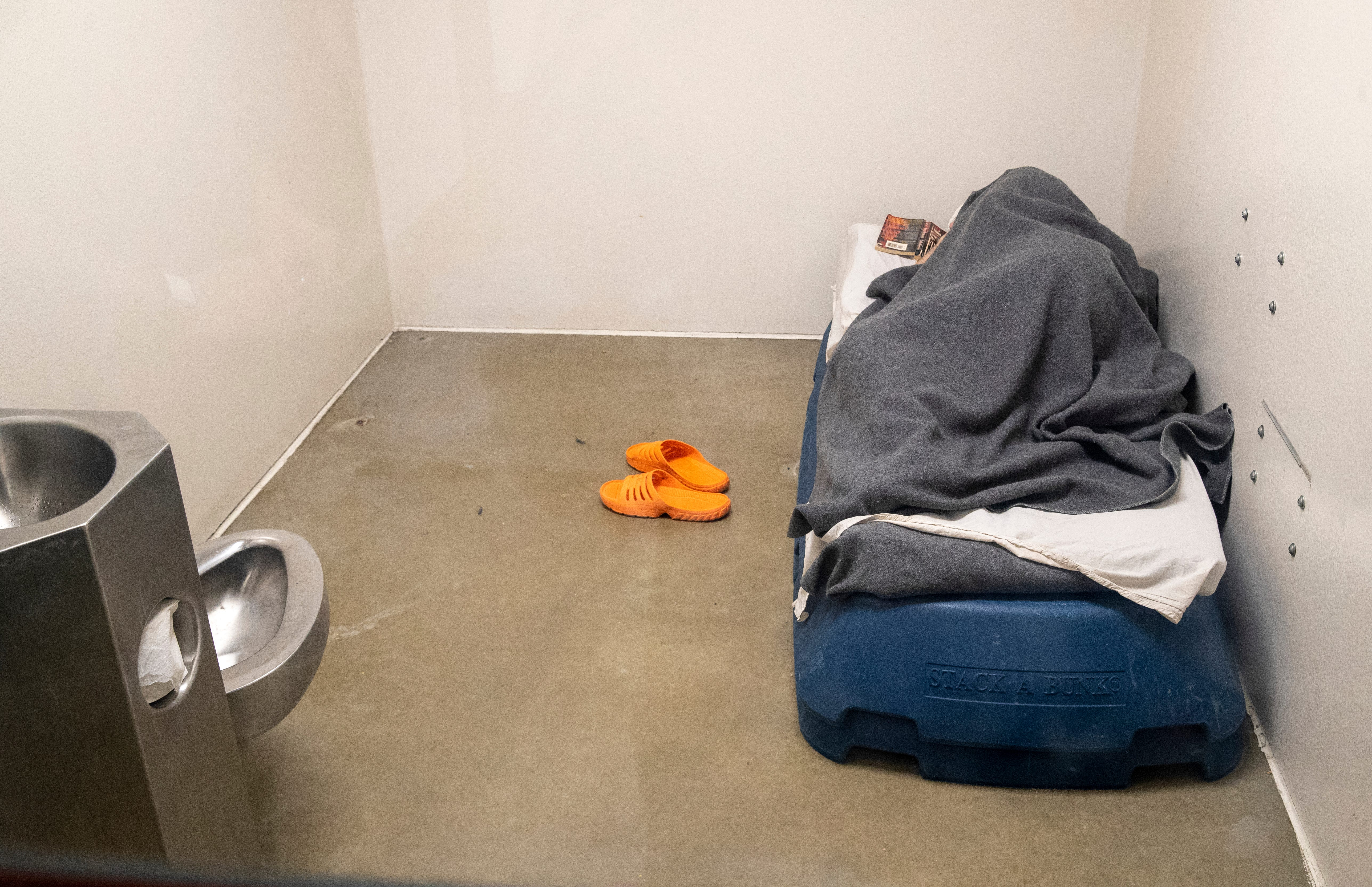 An inmate reads a book in a single cell Wednesday, July 28, 2021, at the Vanderburgh County jail in Evansville, Ind. While it is one of the larger county jails in Indiana, it has only had three deaths — all of natural causes — since 2010.