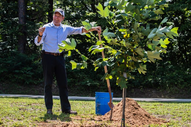 Tennessee Agriculture Commissioner, Charlie Hatcher, prepares to add soil during a ceremonial tree planning for a  Division of Forestry work center on Natchez Trace State Forest on Tuesday, Aug 3, 2021 in Wildersville, Tenn.