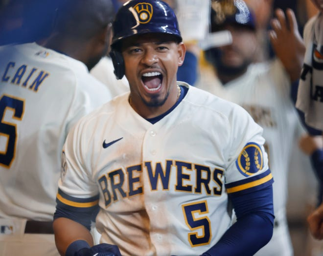 Eduardo Escobar celebrates in the Brewers dugout after his three-run home run against the Pirates during the seventh inning Monday.