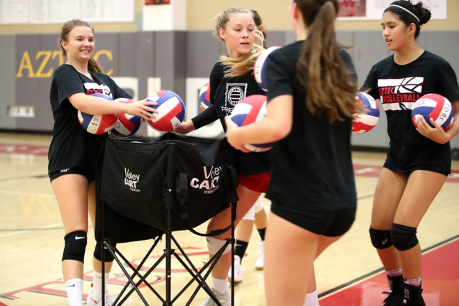 Palm Desert High School volleyball teammates rush to collect the balls during practice at the school in Palm Desert, Calif., on August 2, 2021. High School volleyball players across the Coachella Valley missed an entire season due to the pandemic.