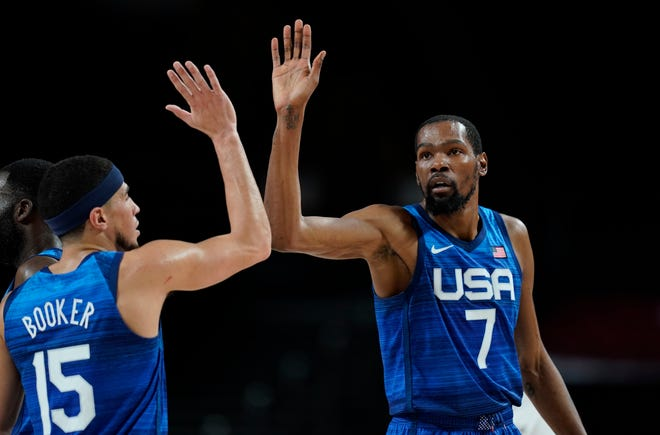 United States' Kevin Durant (7), right, celebrates with teammate Devin Booker (15) after a dunk during men's basketball quarterfinal game at the 2020 Summer Olympics, Tuesday, Aug. 3, 2021, in Saitama, Japan. (AP Photo/Charlie Neibergall).