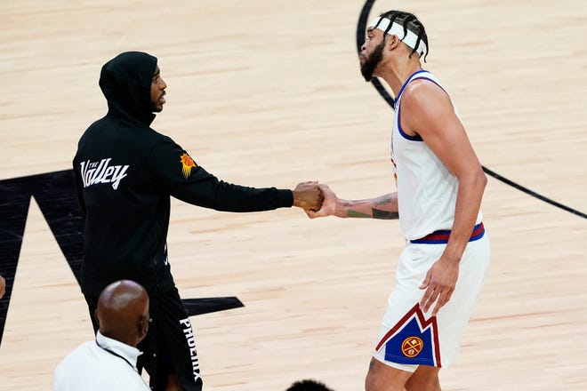 Phoenix Suns guard Chris Paul, left, greets Denver Nuggets center JaVale McGee after Game 2 of an NBA basketball second-round playoff series, Wednesday, June 9, 2021, in Phoenix. The Suns won 123-98. (AP Photo/Matt York).