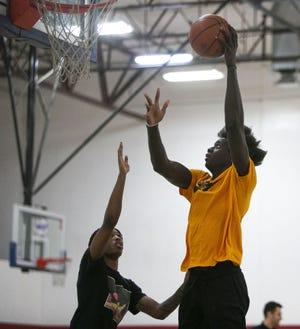 Jan. 18, 2021; Gilbert, AZ, USA; Hillcrest Prep's Mouhamadou Cisse (right) shoots a basket at Hillcrest's practice at Inspire Courts. Credit: Meg Potter/The Arizona Republic