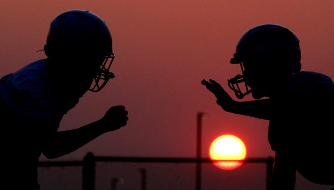 Players on the Wall High School football team practice as the sun comes up Tuesday, Aug. 3, 2021.