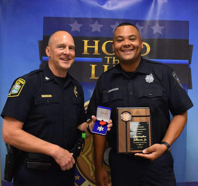 Waynesboro Police Chief Michael Wilhelm, left stands with Officer Christopher Johnson after presenting Johnson with a medal and plaque for saving the life of a man in mental crisis on the South River bridge June 3.