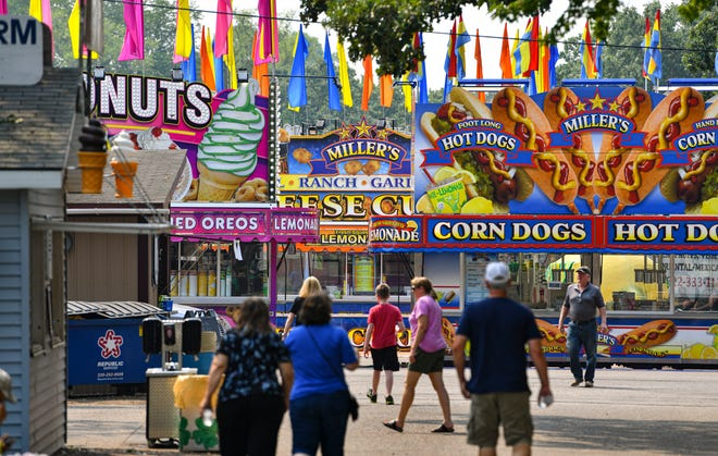 People walk by several fair food stands ready for business Tuesday, Aug. 3, 2021, at the Benton County Fair in Sauk Rapids.