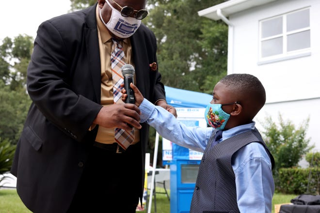 Leon County School Board member Darryl Jones hands the microphone to Caleb Stewart, 7, at Alarm International Church on Tuesday morning. Stewart, the CEO of Master Caleb's Discovery Library, is the youngest member of the Greater Tallahassee Chamber of Commerce and the Capital City Chamber of Commerce.