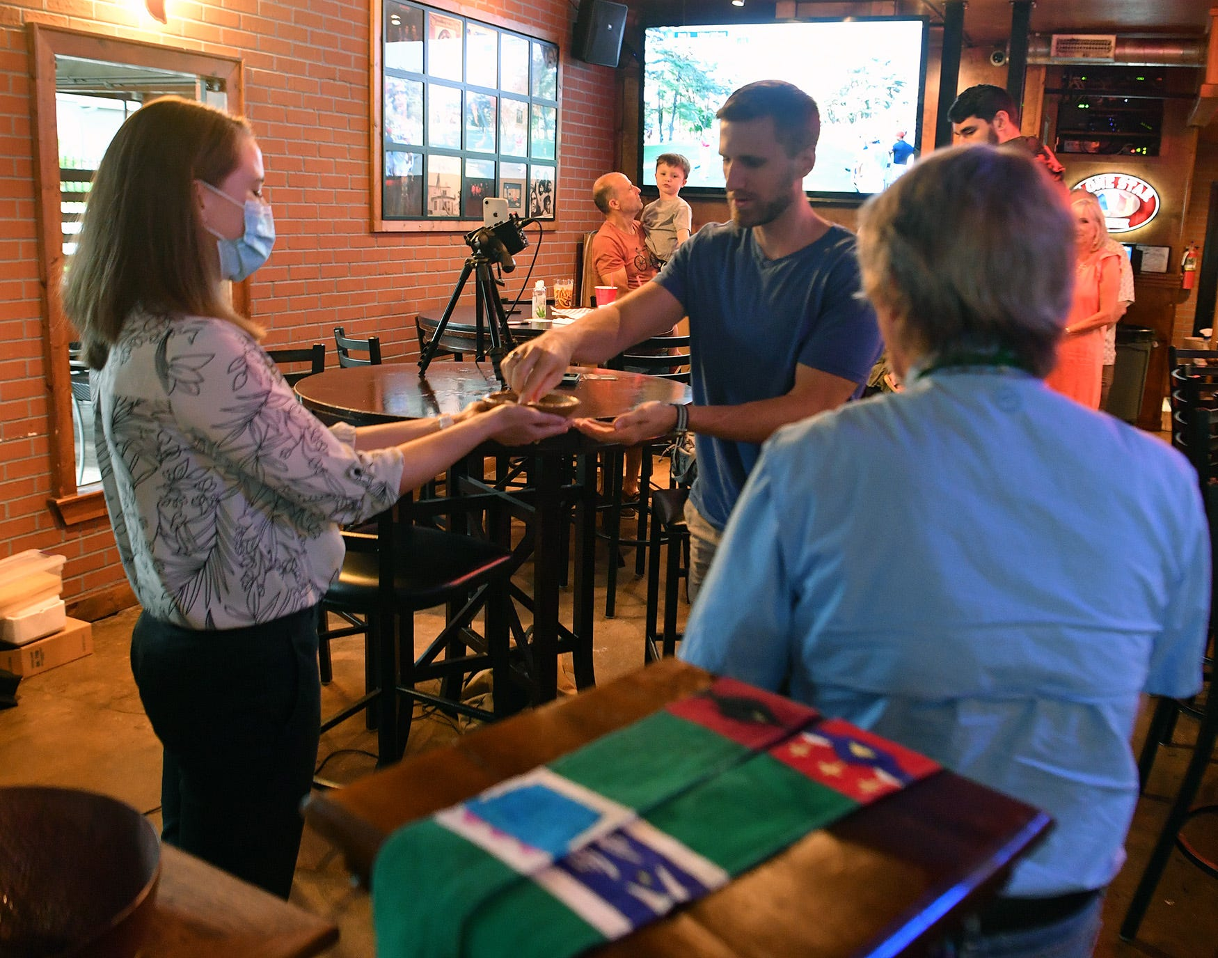Rev. KristinKlade, left, hands out communion to a worshiper during the Lutheran-based Kyrie Pub church service in Fort Worth, Texas.