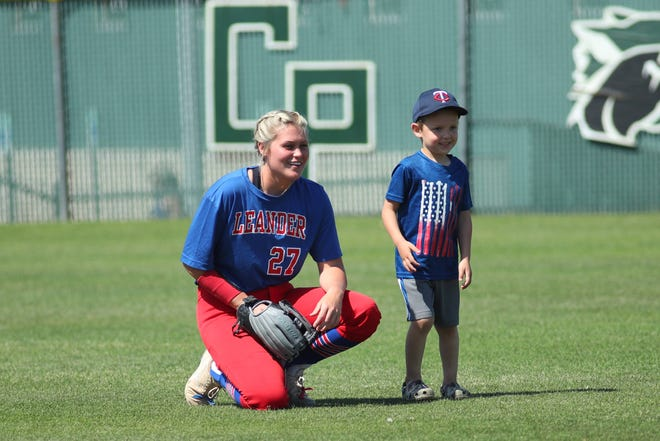 Leander center fielder Baylea Brandon chats with a young fan prior to a district game against Cedar Park in April. Brandon earned a spot on the Class 6A first-team, all-state softball team from the Texas Sports Writers Association.