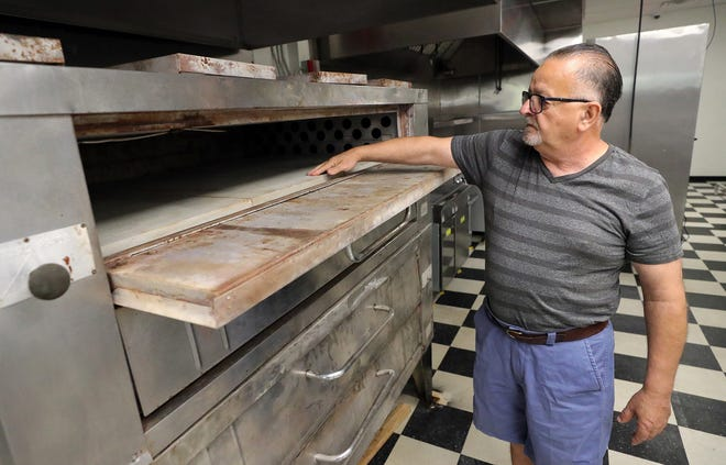 Renato Serpico, owner of Luca's Pizza, shows off one of the pizza ovens, Friday, July 30, 2021, in Stow, Ohio.
