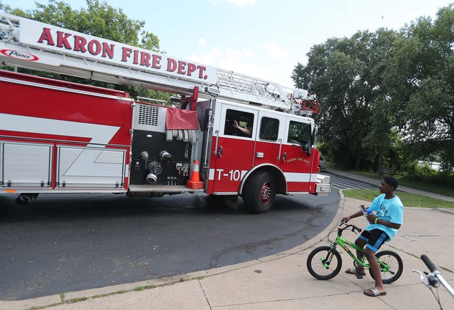Members of Akron Fire Department Station 10 wave to attendees of the Night Out Against Violence at the Summit Lake Community Center on Tuesday.