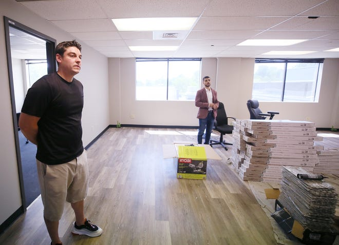 Fred Guerra, co-owner of Jetpack, left, and Ash Abbas, president, tour the former Waltco building as they talk about the renovations in the office area on Monday Aug. 2, 2021. The company's  Akron-based vitamin/nutrient fulfillment distribution center is moving to Tallmadge facility.