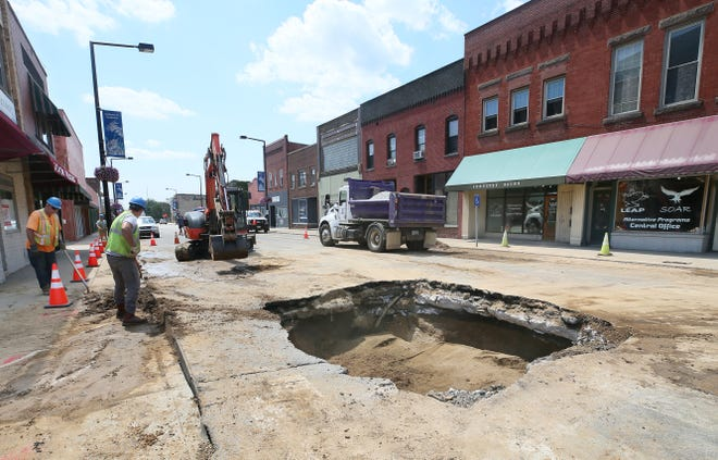 Barberton City Service Dept. workers get ready to fill in a hole that they created to fix a water main break Wednesday on 2nd Street NW and West Paige Avenue. The break was on the side of the pipe and caused extensive road buckling on 2nd Street.