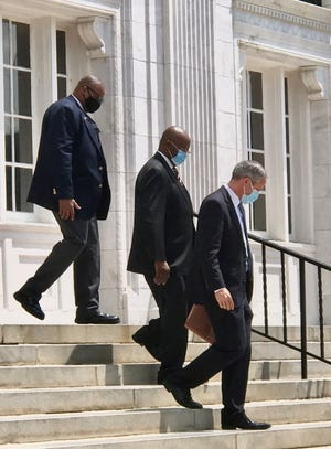 Augusta Commissioner Sammie Sias, center, walks out of the U.S. District Courthouse with attorney David Stewart, right, and a bailiff after a Wednesday hearing.