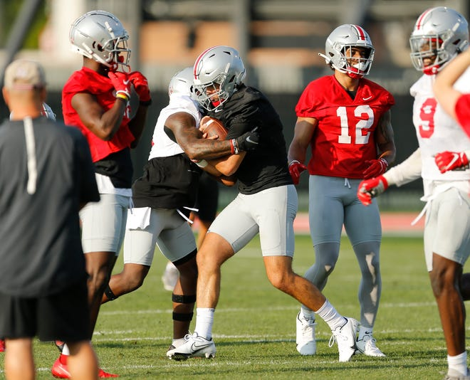 Jack Miller, here rushing with the ball during camp, says he and fellow quarterbacks C.J. Stroud and Kyle McCord have a great relationship.