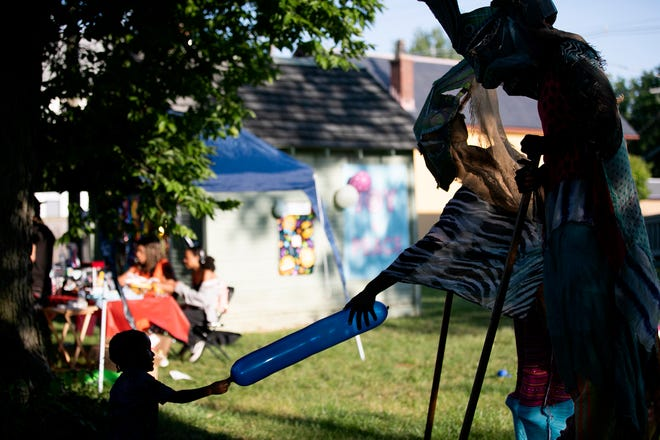 """Jason Larry Jr., 2, tries to share his balloon from a """"safe distance"""" with the Mokko Jombie (Guardian Spirits) stilt walkers from Afrakan Artist Alliance, of Cincinnati, during a National Night Out event in Driving Park hosted by Rickenbacker Woods Foundation Tuesday."""
