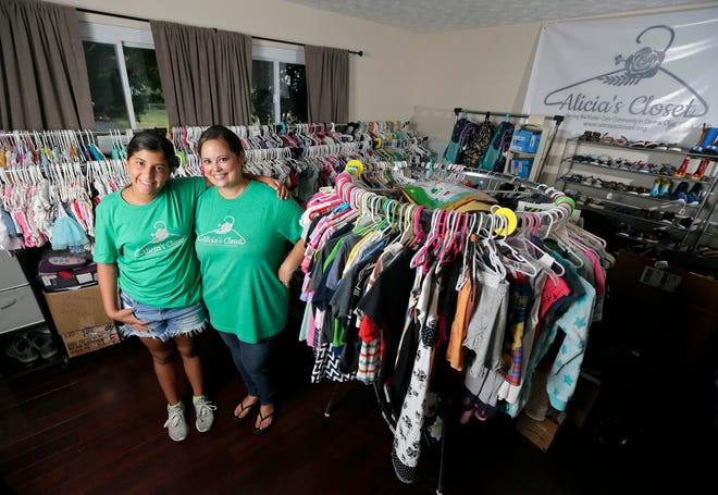 Maya Ward, right, and her 11-year-old daughter, Alicia, the namesake for the nonprofit Alicia's Closet, in their Reynoldsburg home, which is set up with racks of clothes and shoes to help foster families.
