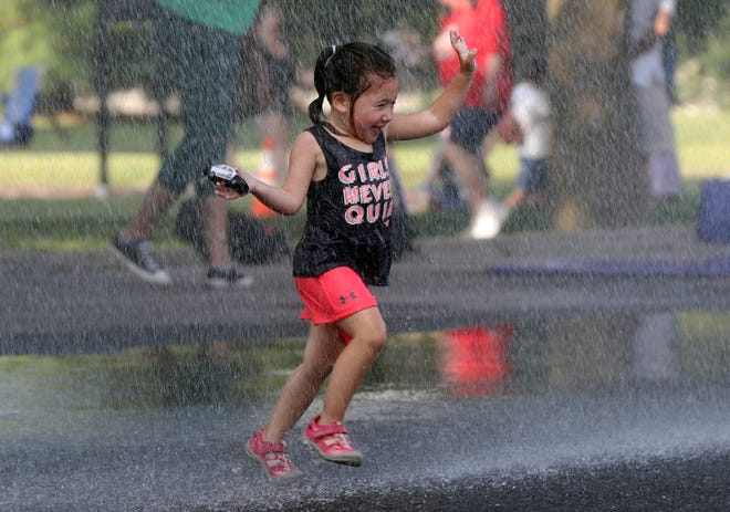 Addie Canale, 2, of Hilliard, runs through water sprayed from a Norwich Township fire truck during National Night Out organized by the Hilliard Division of Police on Aug. 3.