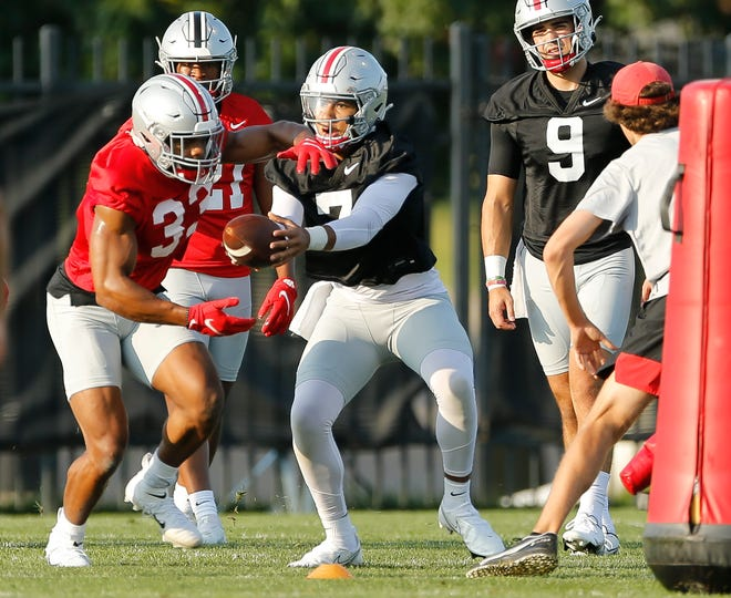 Ohio State Buckeyes quarterback C.J. Stroud hands off to running back Master Teague III during the first practice of fall camp.