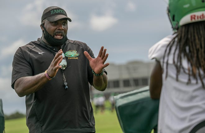 Lake Minneola High School football coach Walter Banks talks with his players on the practice field Tuesday at Lake Minneola High School in Minneola. [PAUL RYAN / CORRESPONDENT]