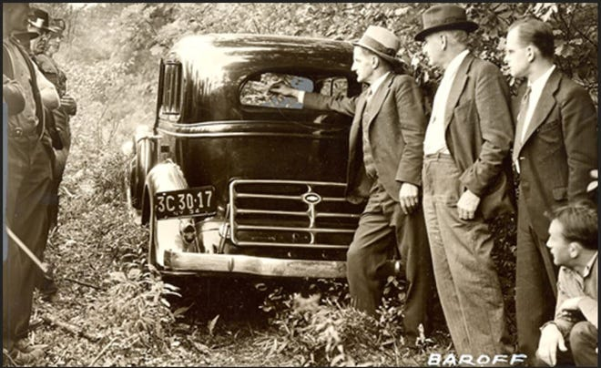 GET-AWAY CAR - Following the armed robbery at the Hawley Bank, September 18, 1934, investigators located the get-away car, a 1933 Chevrolet sedan, about three miles from Hawley. Sheriff John A Foster, of Wayne County, is shown pointing to the fact that the rear window had been broken out, indicating the bandits were ready for a gun battle with possible pursuers. Courtesy The Times-Tribune, Scranton. /Contributed photo