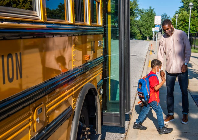 Brandon McGhee, Fairview Elementary family and community engagement coordinator, fist bumps a student Aug. 4 at Fairview on the first day of the new school year. Area fathers, father figures, mentors and role models welcomed Fairview students.