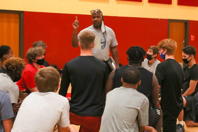 Lejeune coach Walter Tatum talks to his players Tuesday as the Devilpups held their first football workout in two years.