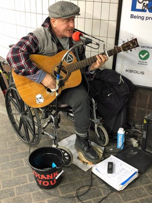 John Whitty of Allston sings in the Park Street MBTA station. Whitty says he performs in many of the stations.