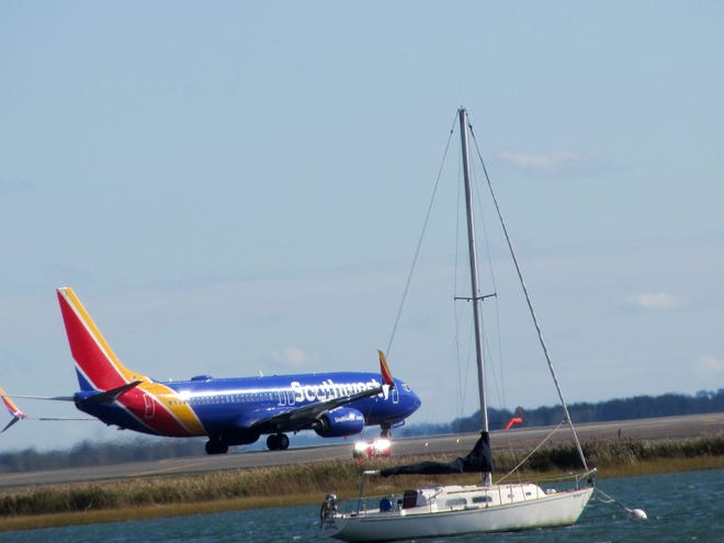 This airplane is waiting for takeoff and the boat is waiting to sail in East Boston.