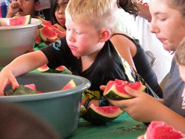 Dayton Casper reaches in for another piece of watermelon during the Arkansas Valley Fair in 2017.